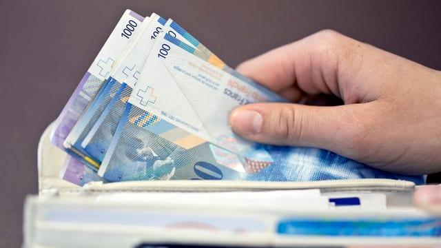 Bancnotas da 100 e 1'000 francs en ina bursa.