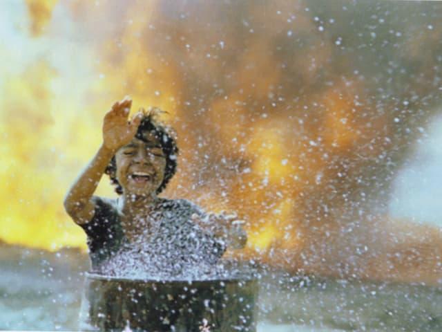 Der Waise Amiru im Film «The Runner», hinter ihm ein Feuer vor ihm eine Blechtonne.