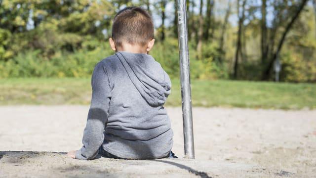 Ein Kind sitzt, den Rücken zugewandt, auf einer Treppe.