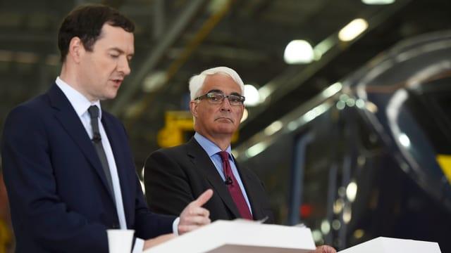 Osborne und Darling sprechen an zwei weissen Rednerpulten in der Halle einer Zugfabrik.