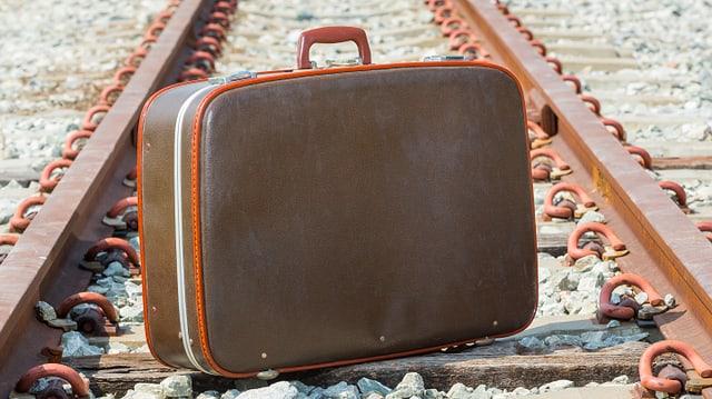 Ein Koffer steht auf dem Schotter zwischen Bahnschienen.