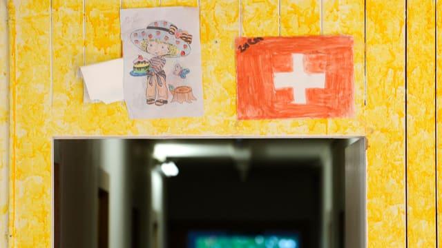 Eingang in ein Asylzentrum mit zwei Kinderzeichnungen.