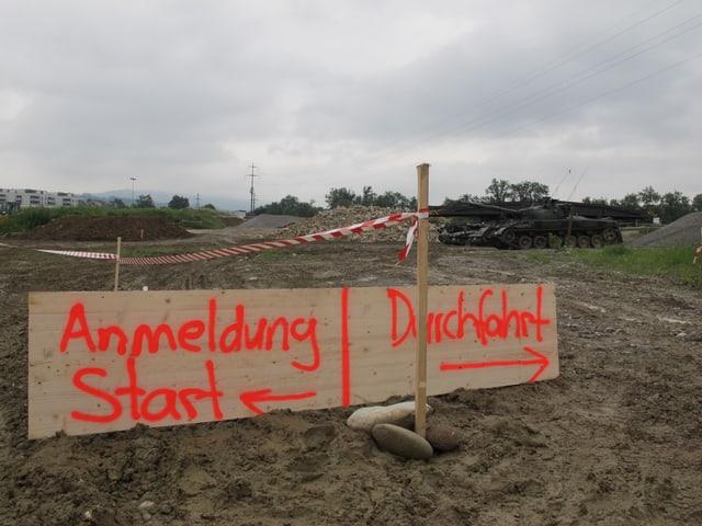 Schild zeigt den Start der Panzerpiste, geschrieben mit oranger Neonfarbe.