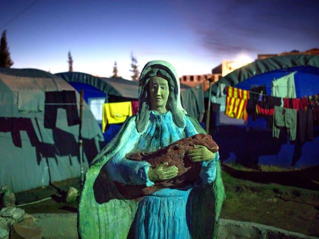 Marienstatue vor den Zelten und Wäscheleinen irakischer Christen auf der Flucht, aufgenommen in der Stadt Erbil 2014.