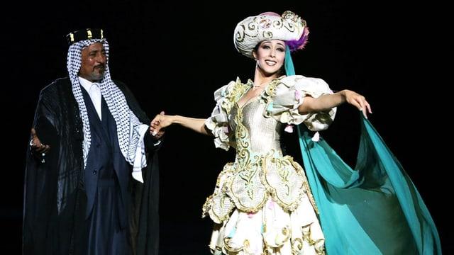 Ein Mann und eine Frau tanzen auf einer Bühne. Sie trägt ein üppiges Kleid mit Hut, er ebenfalls.
