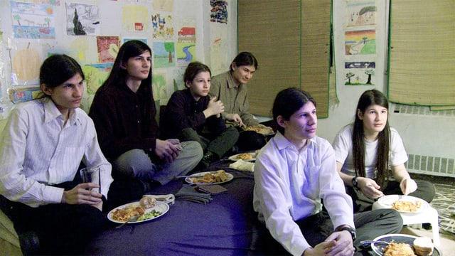 Sechs Jugendliche, die Fernseh schauen und gleichzeitig essen.
