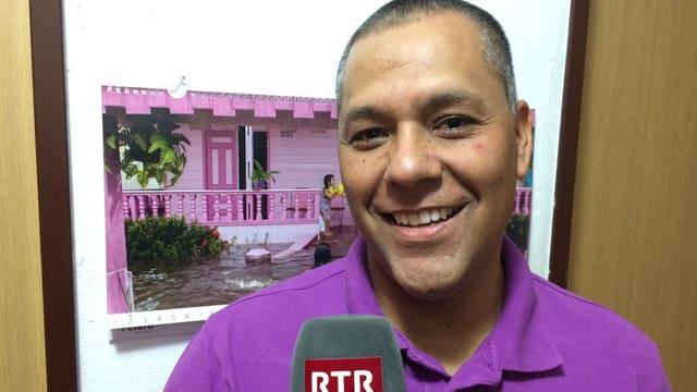 Alejandro Arias Linares ha en maun in microfon dad RTR. El surri e la camera. Davostiers in chalender cun ina chasa rosa. A