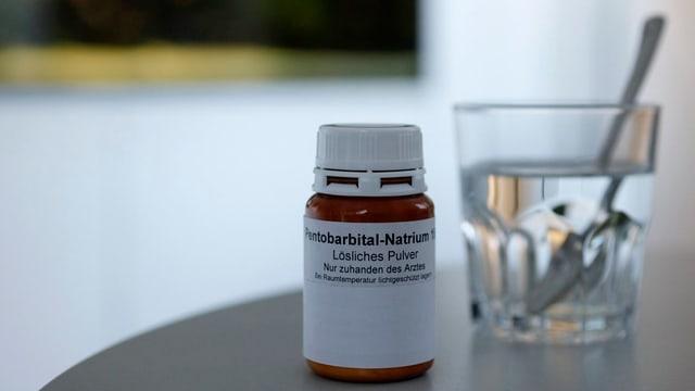 Symbolbild: Eine Medikamentendose, angeschrieben mit Pentobarbital Natrium, daneben steht ein Glas Wasser mit einem Löffel.