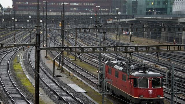 Einfahrt in den Basler Bahnhof, rechts eine rote Lokomotive der SBB