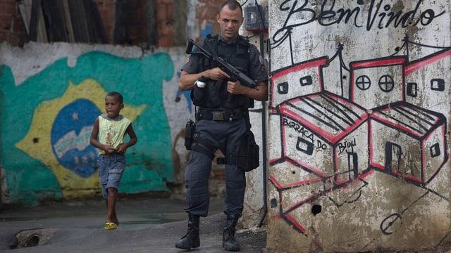Ein schwer bewaffneter Polizist einem Armenviertel Rios hinter ihm ist ein kleiner Knabe zu sehen.