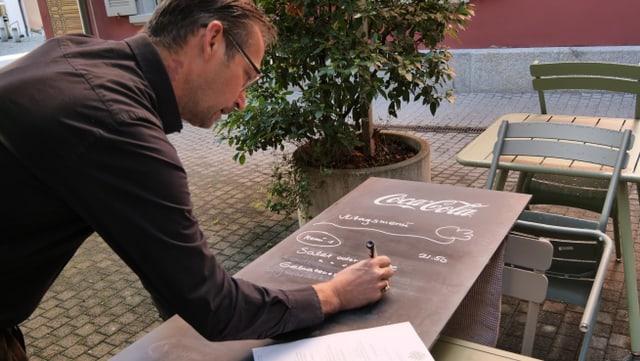 Mann schreibt auf Tafel Mittagsmenue auf