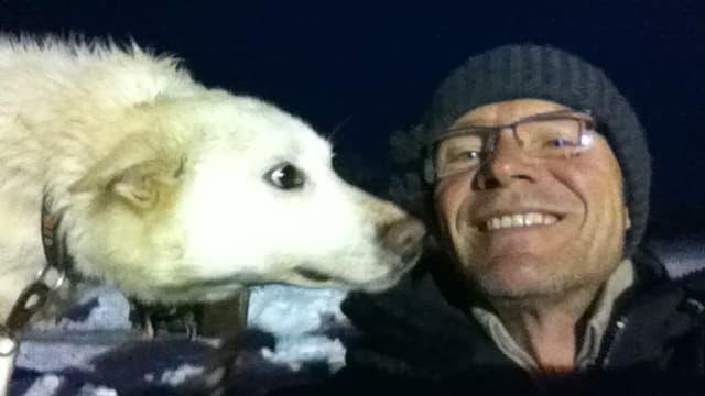 Ein Hund schnüffelt an einem Mann mit Mütze.