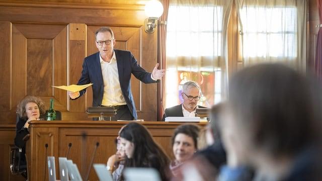 Ein Mann steht im Rathaus hinter dem Rednerpult und spricht zum Parlament.