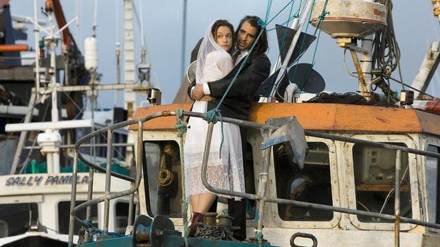 Ein Mann umarmt eine Frau in Hochzeitskleidern auf einem Boot.