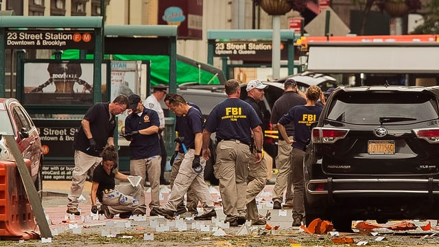 Policists da l'FBI en uniforma vid intercurir la scena.