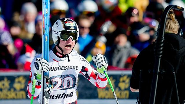 Hannes Reichelt en dress d'ir cun skis e spievel grond da sulegl