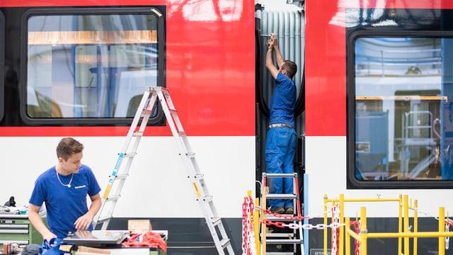 Lavurers lavuran vi d'in tren nov tar la Stadler Rail.
