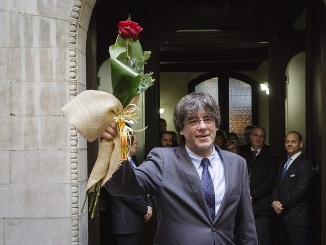Puigdemont jubelt mit einer Rose.