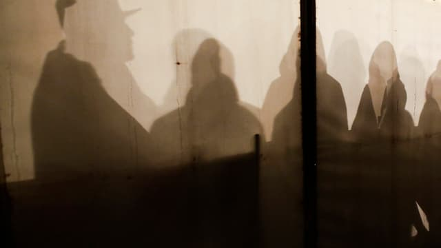 Siluettas da fugitivs che spetgan en ina tenda a Berlin.