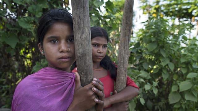 Zwei Mädchen halten sich an Holz fest.