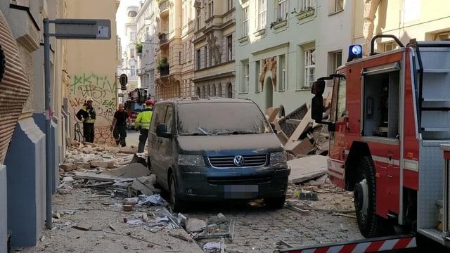 Man sieht ein schwarzes Auto und ein Feuerwehrautto auf einer Strasse. Trümmer und Staub liegen herum.
