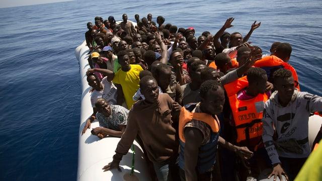 Dutzende afrikanische Migranten in einem Gummiboot auf em Meer.