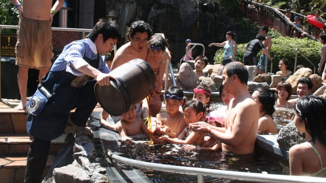 In einem Bassin sitzen eine Gruppe Kinder und Erwachsene und halten ihre Hände aus. Ein Angestellter leert ihnen Kaffee ins Badewasser.