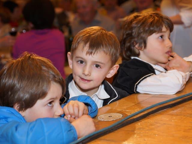 Drei kleine Jungs stützen sich mit den Ellbogen auf der Bühne ab.