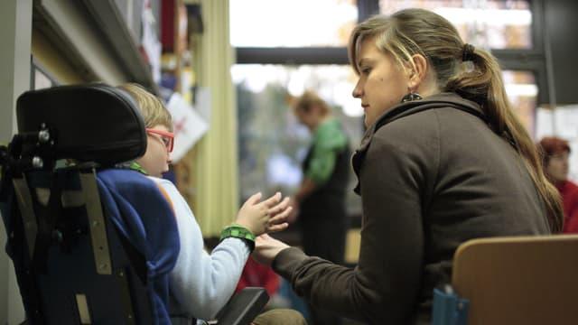 Pflegerin hält Hand von Kind im Rollstuhl