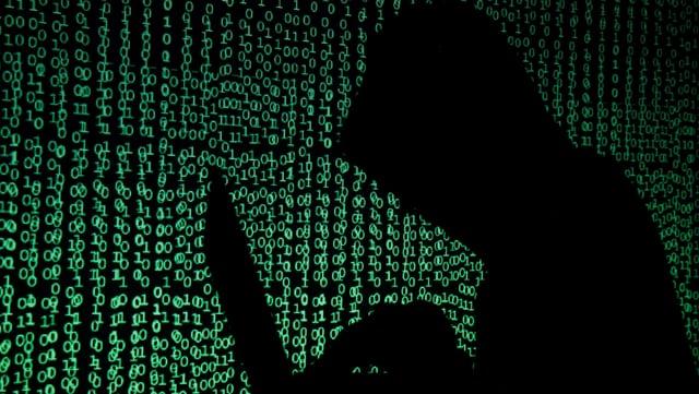 Symbolbild: Ein Mann sitzt an einem Laptop, im Hintergrund grüne Einsen und Nullen.