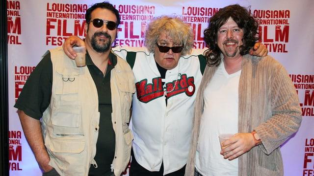 Drei Männer posieren für das Foto in einer Reihe. Derjenige rechts und derjenige links sind als zwei Charaktere aus dem Film verkleidet, in der Mitte steht Jwff Dowd mit Hemd und Sonnenbrille.