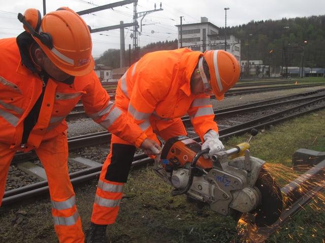 Gleisbau-Anwärter zerschneidet eine Schiene.