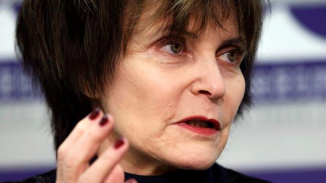 Kopf von Alt Bundesrätin Micheline Calmy-Rey, sie schaut zur Seite, ihre Hände sind gestikulierend erhoben.