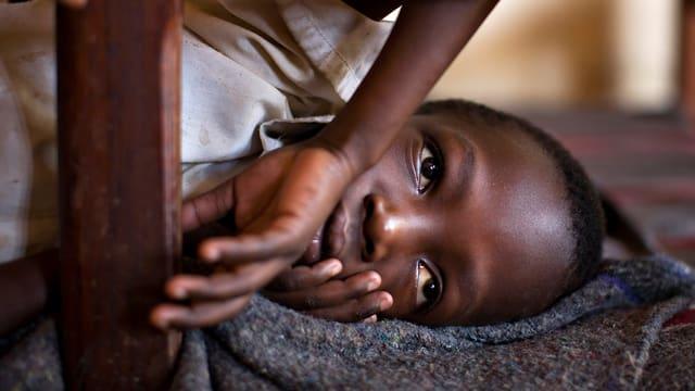 Kriegs-Waise im Kongo luegt am Boden.