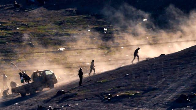 Männer laufen einen Hügel hoch, dahinter ein Lastwagen.