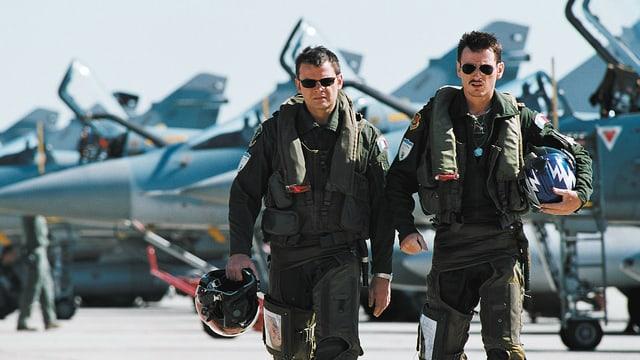 Zwei Piloten gehen vor einer Reihe Kampfjets.