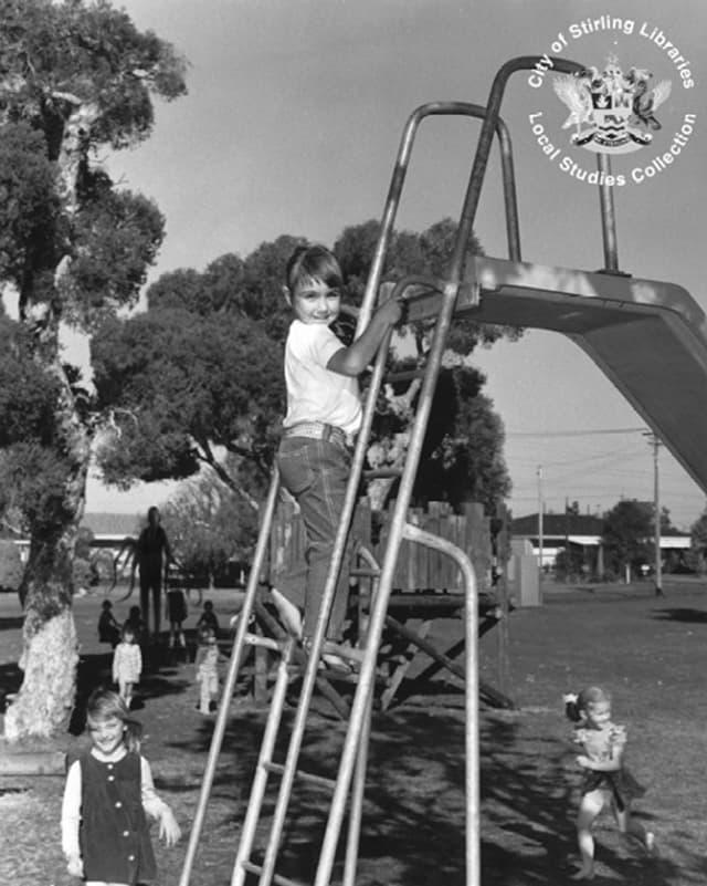 Kinder spielen auf einem Spielplatz. Im Hintergrund die Umrisse eines grossen dünnen Mannes.