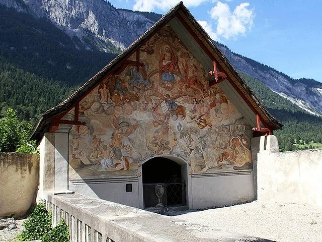 Kleines Haus neben Friedhof mit Wandbemalung.