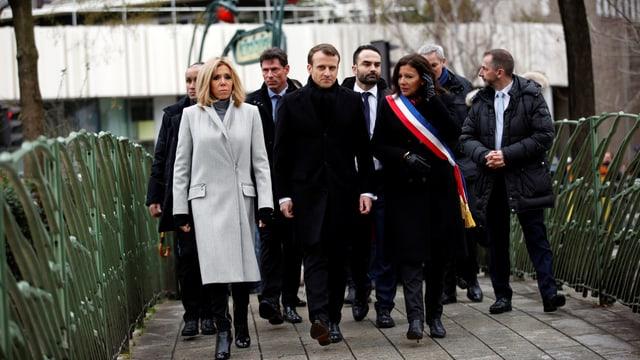 Macron und weitere Personen zu Fuss unterwegs.