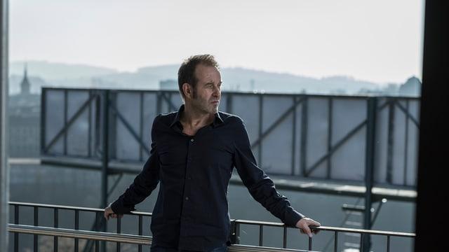 Mann leht an Geländer eines Balkons.