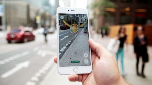 Blick auf eine Strasse über ein Smartphone, das ein Pokémon auf der Strasse anzeigt.