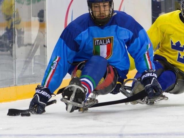 Eishockeyspieler sitzen auf  einem Schlitten