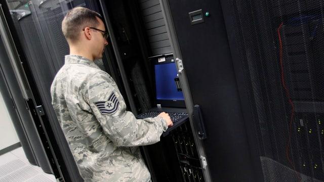 Ein Unteroffizier steht an einem Terminal vor einer Serverwand.