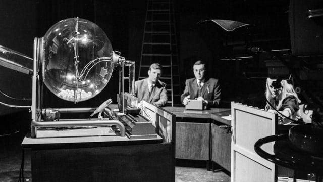 Schwarzweiss-Aufnahme von drei Offiziellen, die gespannt auf die Lottoziehungsmaschine blicken
