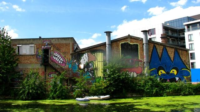 Mit Graffitti beschmiertes, verfallendes Industriegebäude am Fluss.