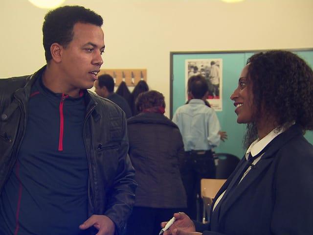 Ein junger Mann und eine Frau sprechen miteinander.