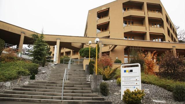 Ein älteres, ockerfarbenes Gebäude (Alterszentrum) mit einer langen Treppe beim Aufgang.