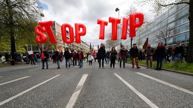 Menschen auf einer Strasse, sie halten grosse rote Buchstaben in die Höhe, welche «Stopp TTIP» bilden.