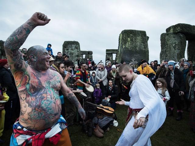Tanzende Menschen vor Steinkreis