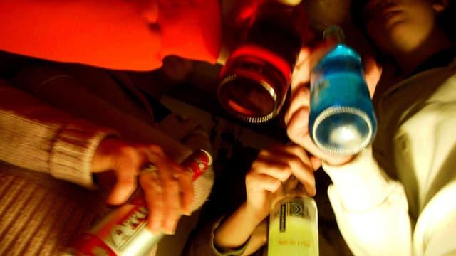 Jugendliche stehen mit Flaschen in einem Kreis.